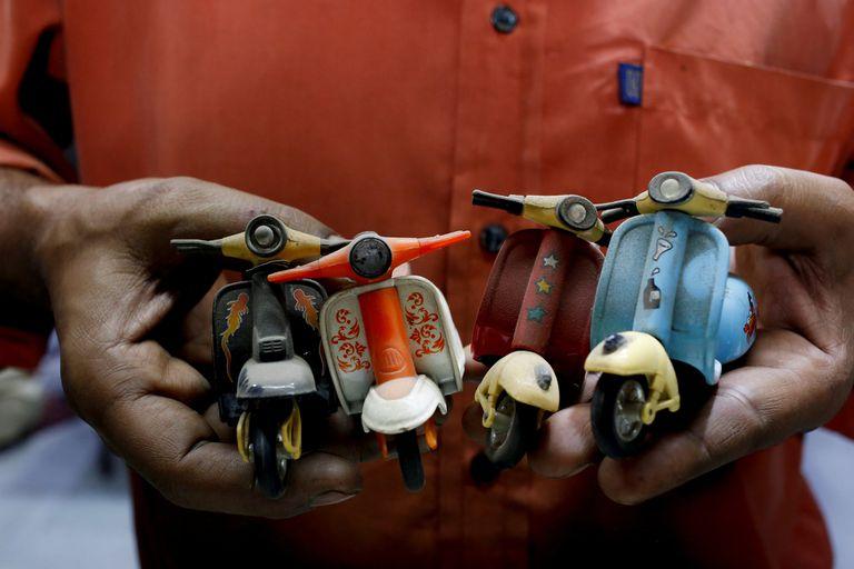 Un tendero y entusiasta de la Vespa tiene su colección de mini recuerdos, en su tienda de autopartes en Karachi,