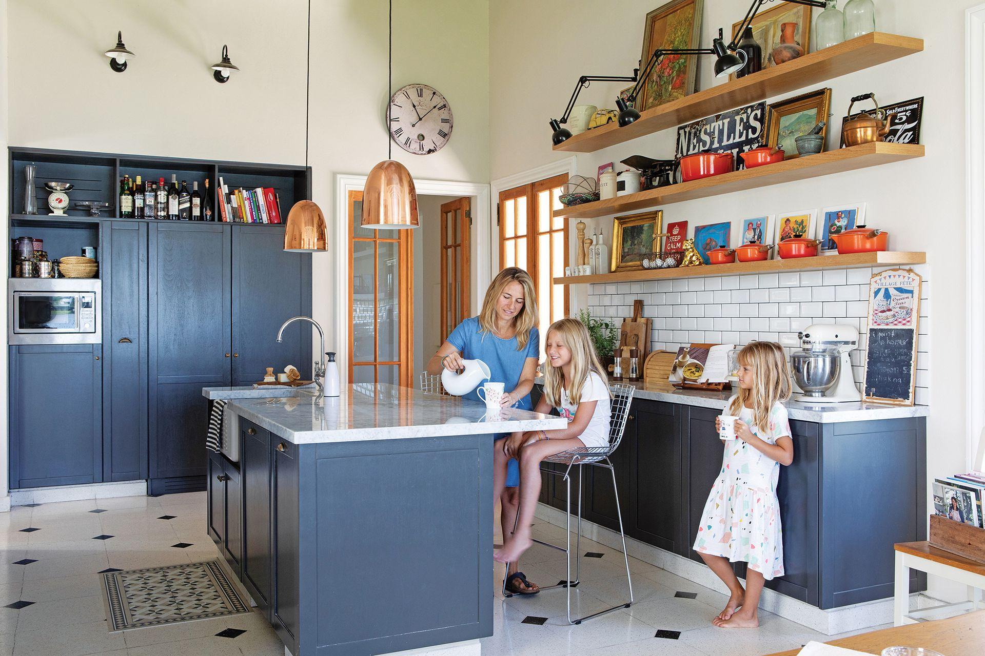 Si los muebles de color oscuro se inspiran en las cocinas inglesas, el piso de mosaico (Blangino) vino por la película Ratatouille: Connie eligió uno granítico con el mismo diseño que el del entrañable film animado. Lámparas colgantes (Díaz Iluminación).