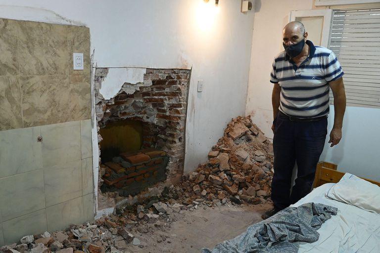 Guillermo Algañaraz, de 62 años, expone el boquete usado por los ladrones para ingresar desde su casa a una empresa de caudales