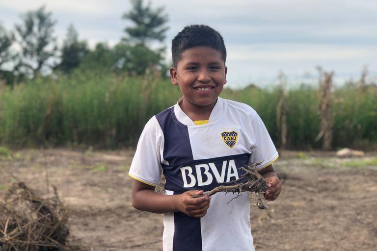Nehuel Rivero ayuda a su papá a limpiar la tierra de la huerta comunitaria en la que trabaja