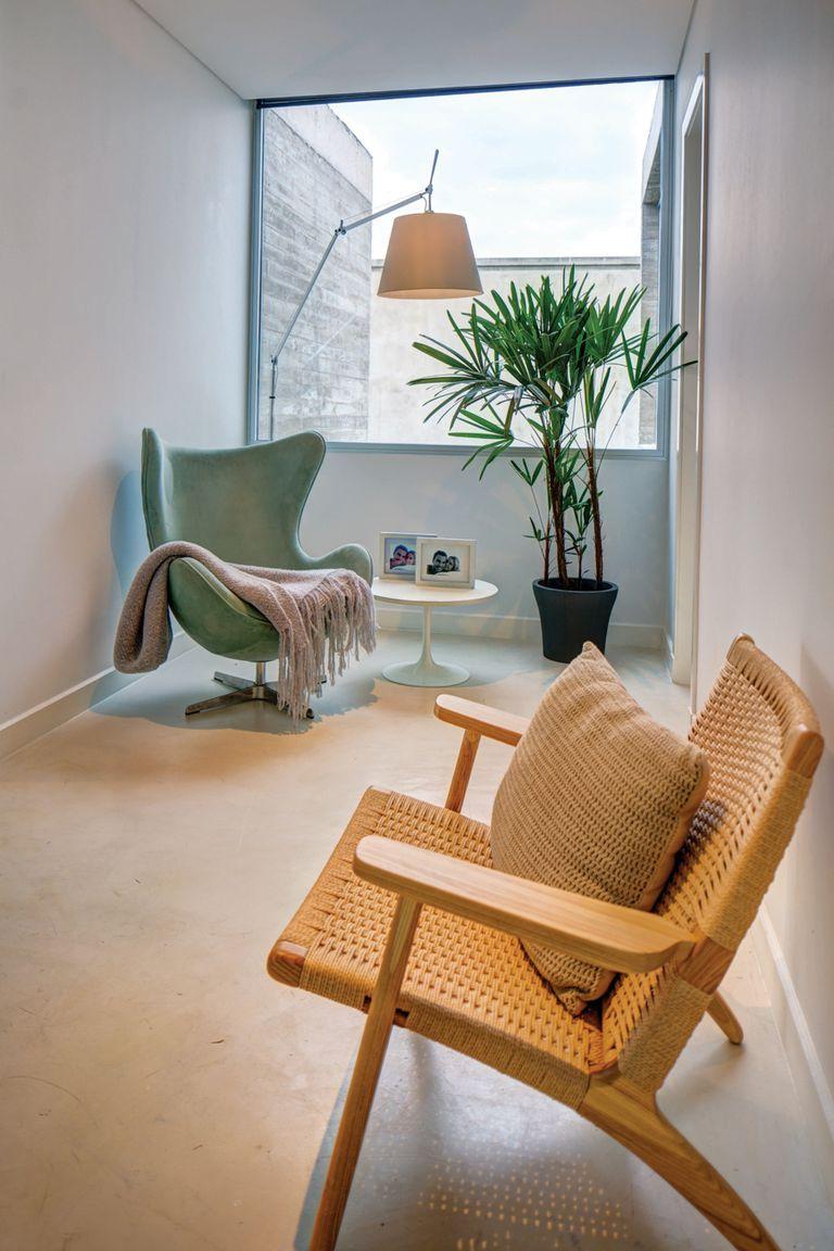 La escalera desemboca en un estar con una silla de mimbre, un sillón modelo Egg Chair y una lámpara modelo Tolomeo, de Fauna Design