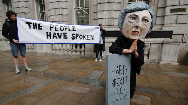 """A demonstrator wears a mask depicting Britain''s Prime Minister and leader of the Conservative Party Theresa May, poses with a mock gravestone bearing the words """"Hard Brexit, RIP"""", during a protest photocall near the entrance 10 Downing Street in central London on June 9"""