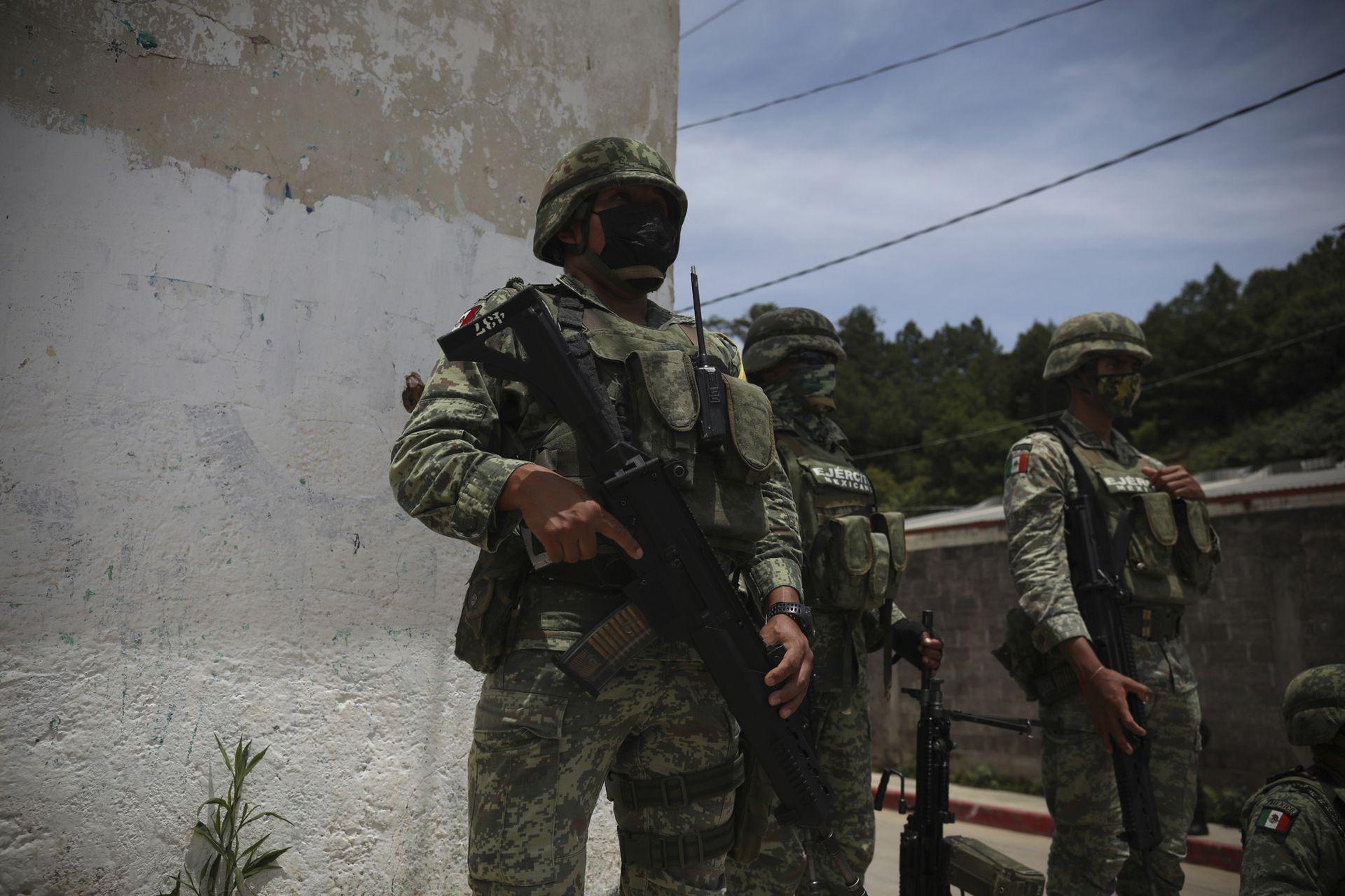 """Soldados del ejército mexicano vigilan el perímetro durante la reunión entre las autoridades locales y los miembros de la agrupación """"El Machete"""""""