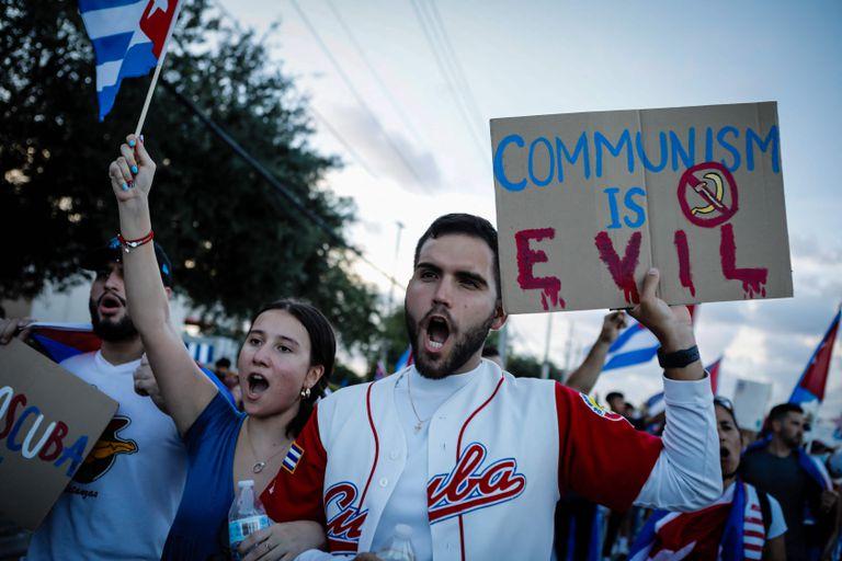 """""""El comunismo es el diablo"""", dice un cartel en una marcha para apoyar a los manifestantes cubanos en Florida"""