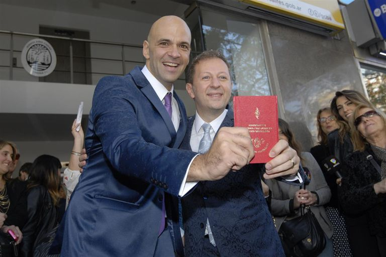 Nicolás Scarpino, libreta en mano, junto a su flamante marido, en 2015