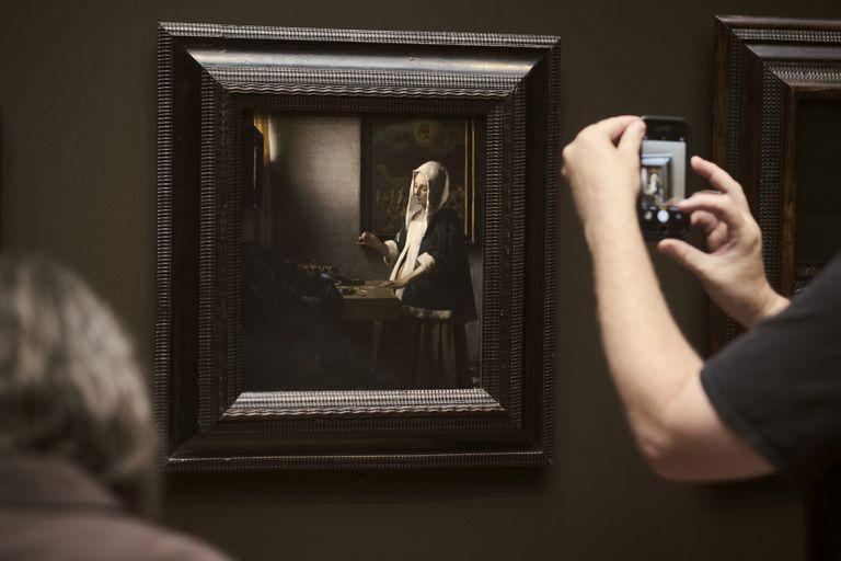 """Un visitante fotografía """"Woman Holding a Balance"""", de Vermeer, en la Galería Nacional de Arte de Washington. Varias obras atribuidas al pintor holandés están actualmente en estudio"""