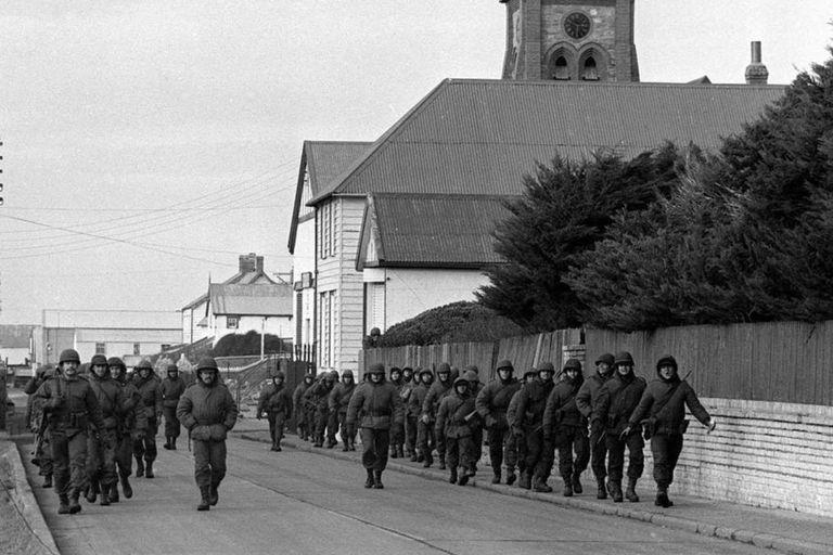 Soldados de Argentina caminan por la Avenida Ross, luego de la toma de las islas Malvinas, en abril de 1982