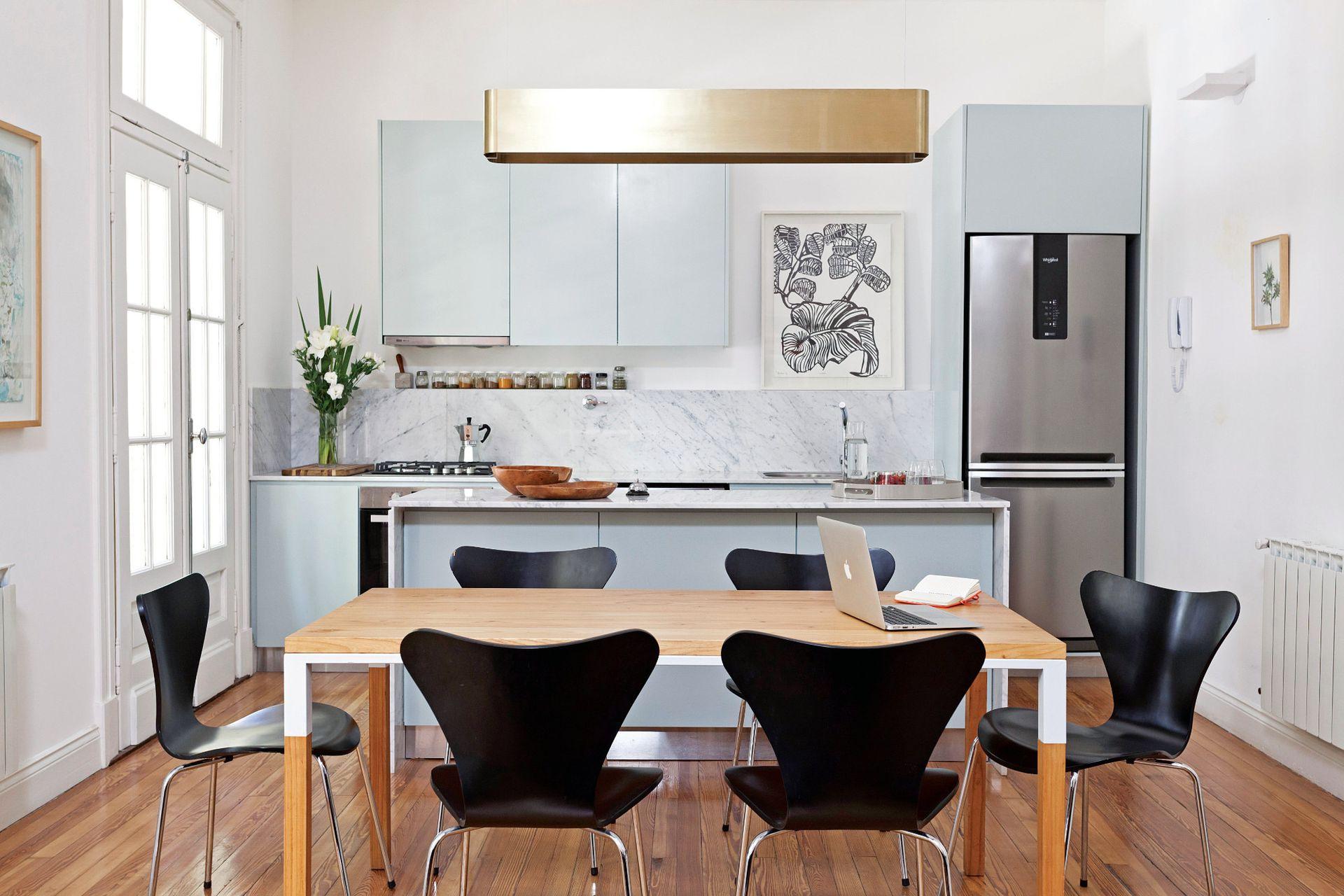 Las sillas negras estilo Jacobsen ayudan a la transición entre el living y la cocina. Sobre la mesa (Números Primos), la estilizada lámpara colgante de bronce (La Feliz) conversa con el cuadro de María Marta Fasoli (Izq.), enmarcado en madera al natural.