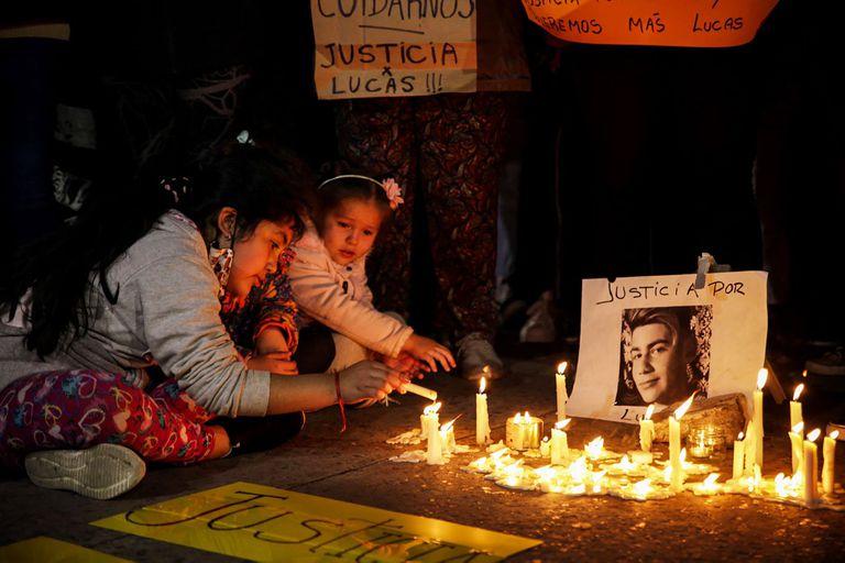 Unas niñas prenden unas velas en homenaje a Lucas en el barrio Naval