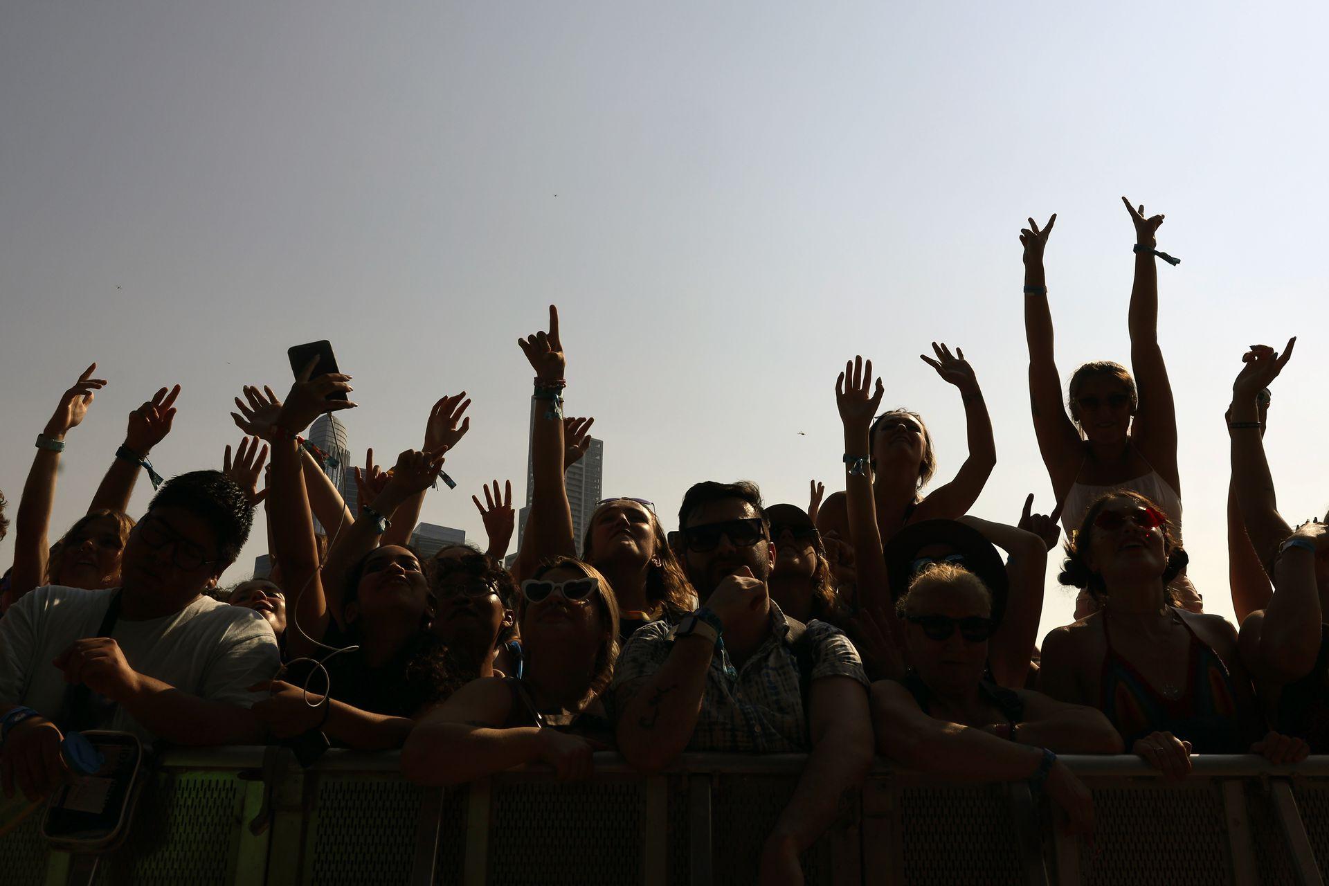 Los fanáticos se recortan contra el cielo mientras vitorean y agitan sus manos en el aire el primer día del festival de música Lollapalooza el jueves 29 de julio de 2021 en Grant Park en Chicago