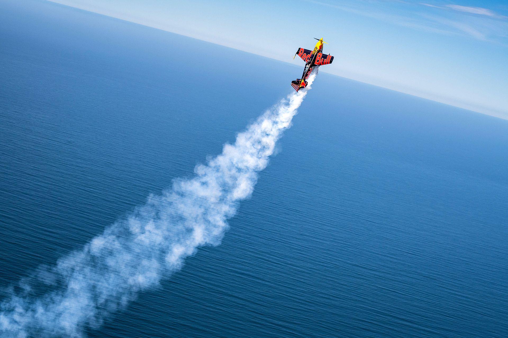 El avión de Kirby Chambliss deja una estela de humo sobre el Oceáno Pacífico