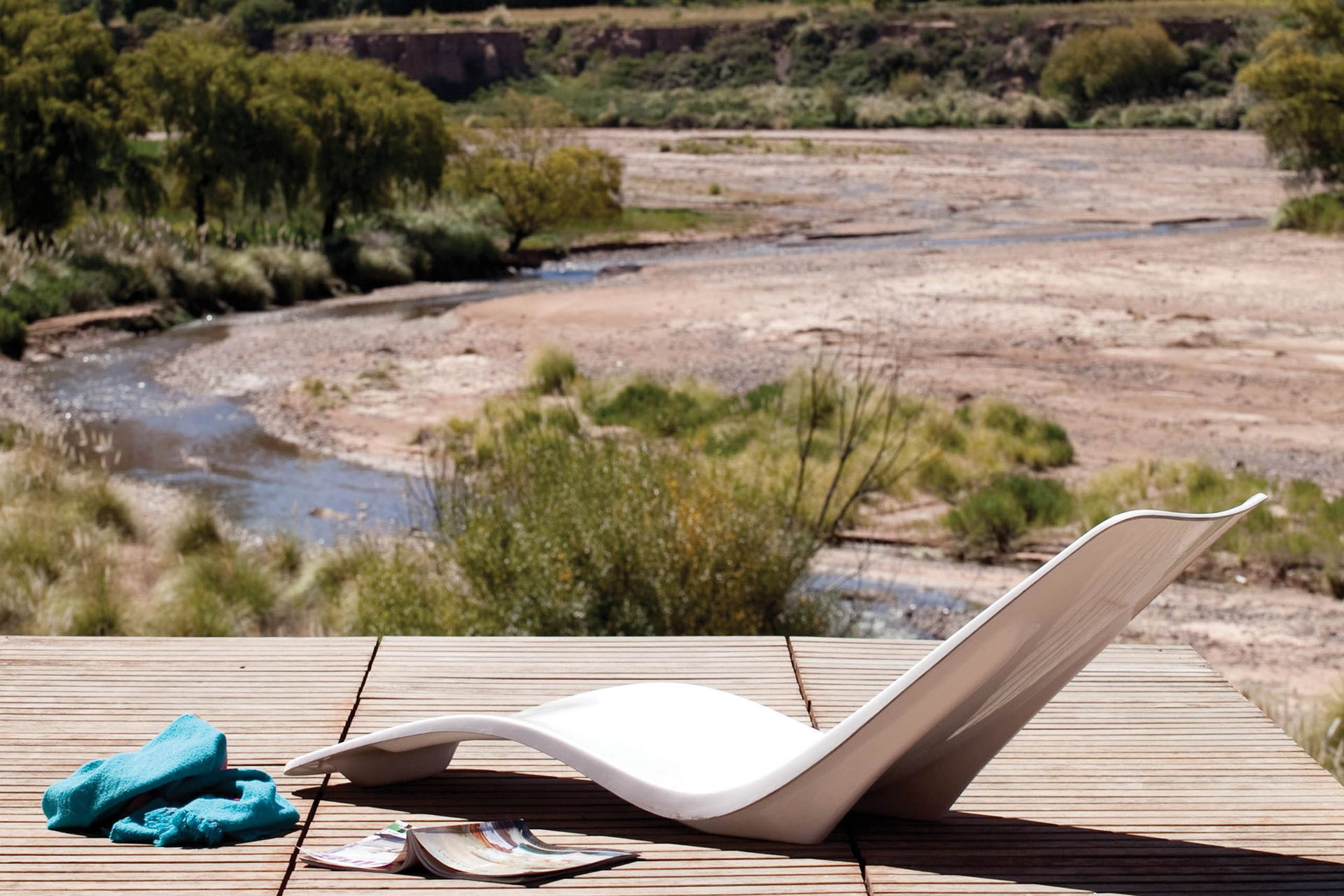Suspendido en el paisaje, un deck prolonga el área de estar para aprovechar el espacio exterior cuando amaina el viento.