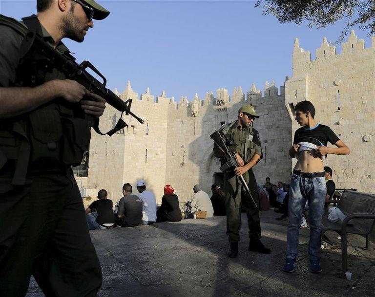 La policía israelí revisa a un joven palestino en la Puerta de Damasco de la Ciudad Vieja de Jerusalén