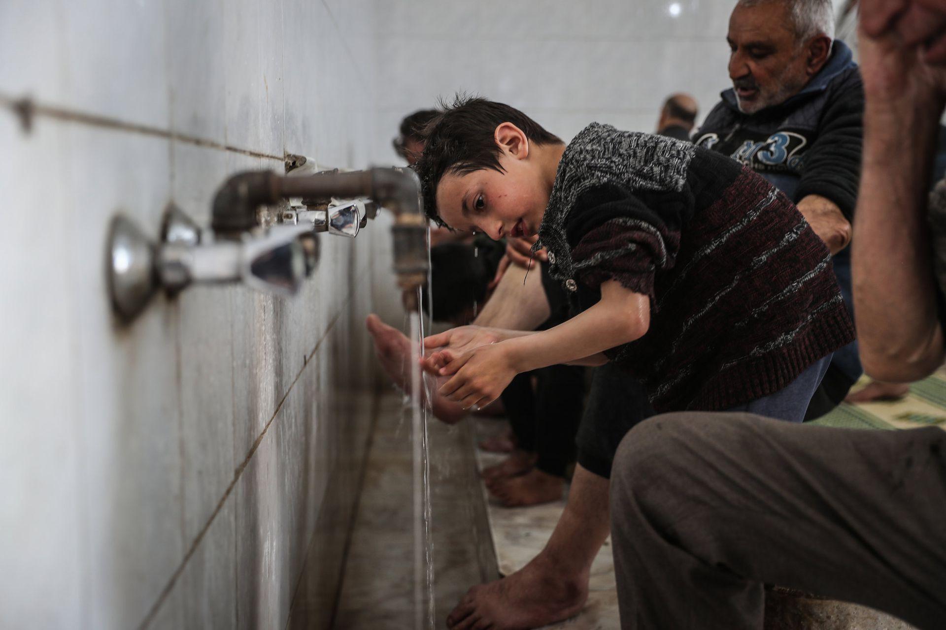 Musulmanes sirios realizan el ritual de limpieza 'Wudu' mientras se preparan para leer el Corán y rezar en la mezquita de la ciudad de Maarrat Misrin