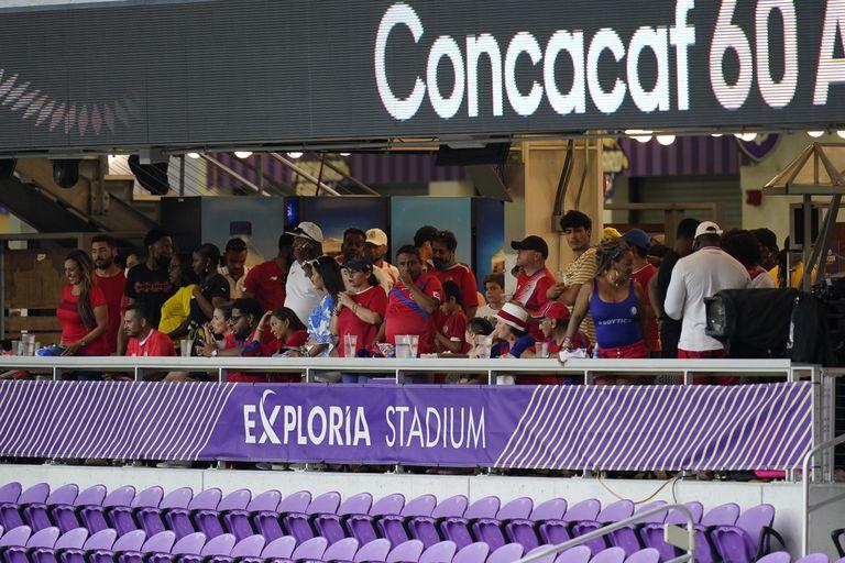 Un grupo de hinchas busca guarecerse durante una interrupción del partido entre Jamaica y Costa Rica en Orlando, Florida, el martes 20 de julio de 2021 (AP Foto/John Raoux)