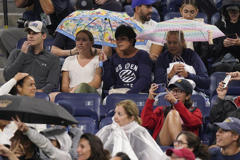 Partido de tenis en estadio techado, pero con paraguas