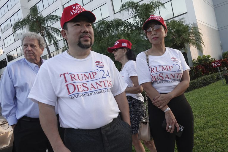Supporters of Florida Gov. Ron DeSantis, Binh Vo, left, and Trang Le, of Orlando, wait in line for his appearance on Fox & Friends, Thursday, May 6, 2021, in West Palm Beach, Fla.  DeSantis has signed a sweeping elections bill into law that he and other Republicans said would place guardrails against fraud, even though there were no signs of voter irregularities in the November presidential election. (Joe Cavaretta/South Florida Sun-Sentinel via AP)