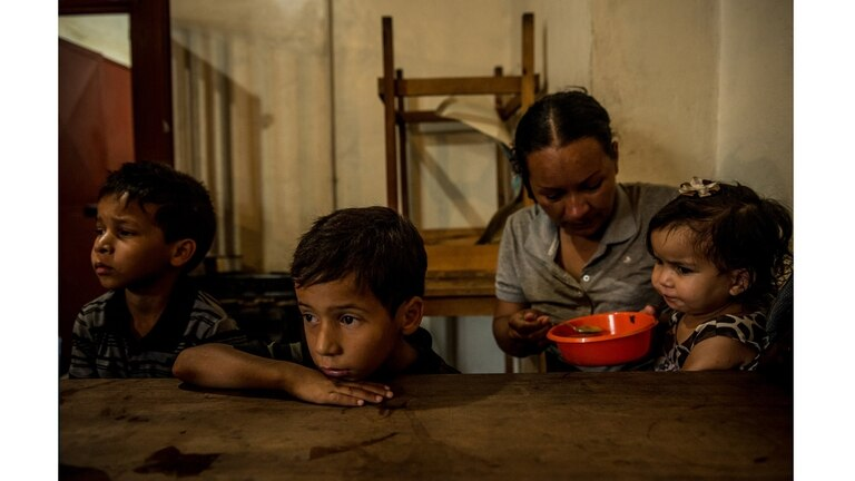 Orianna Caraballo dándole de comer a Brayner, Rayman y Sofía, sus hijos, en una cocina comunitaria en Los Teques, en septiembre
