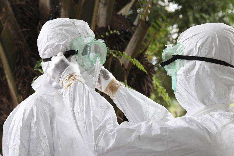Dos enfermeros liberianos revisan sus equipos de protección antes de transportar el cuerpo de una víctima del ébola para su entierro