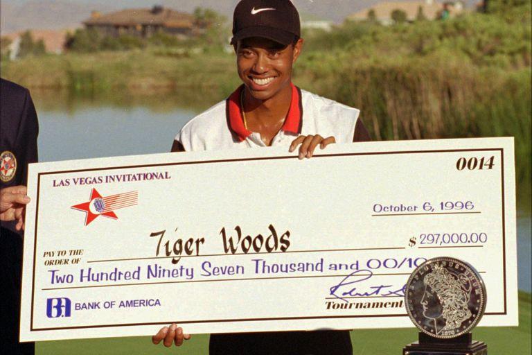 ARCHIVO - En esta fotografía de archivo del 6 de octubre de 1996, el golfista profesional novato Tiger Woods sonríe después de recibir un cheque y un trofeo por ganar el torneo de golf Las Vegas Invitational en el TPC en Summerlin en Las Vegas. Hace veinticinco años esta semana, Woods ganó por primera vez en el PGA Tour en el Las Vegas Invitational, cambiando el golf para siempre. (Foto AP / Lennox McLendon, archivo)