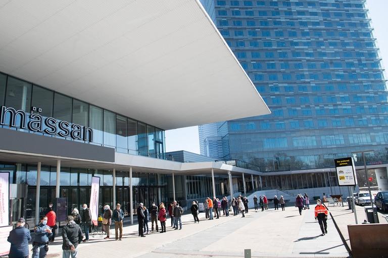 Las personas hacen fila para vacunarse contra el Covid-19 fuera del centro de exposiciones Stockhomsmassan convertido en un centro de vacunación en Estocolmo, Suecia