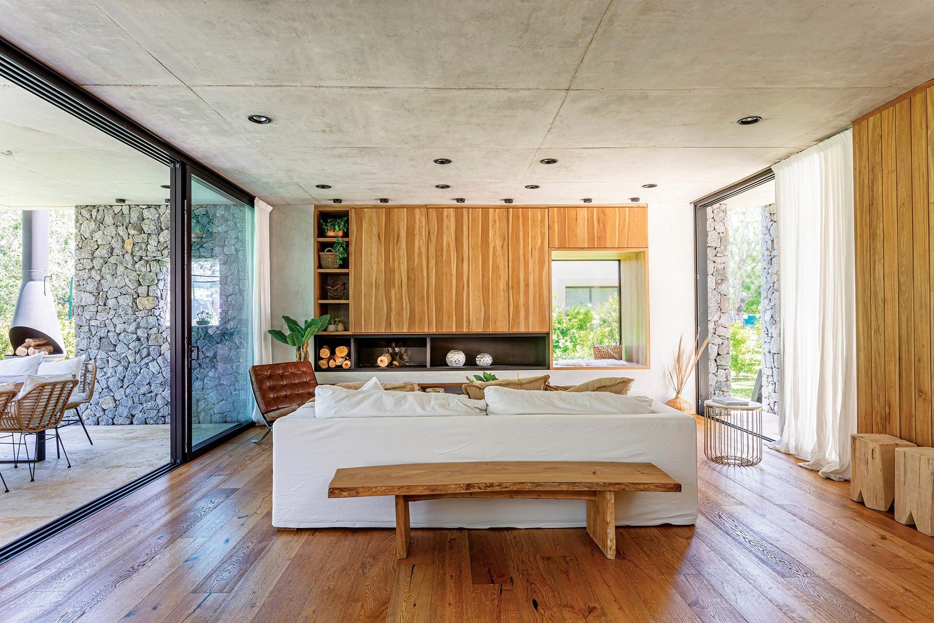 Detrás del sofá, un banco de madera maciza (carpintero Pablo Amadeo) hace juego con el piso de roble labrado (Patagonia Flooring). La chimenea de hierro se diseñó integrada al frente y forma una L con los estantes.