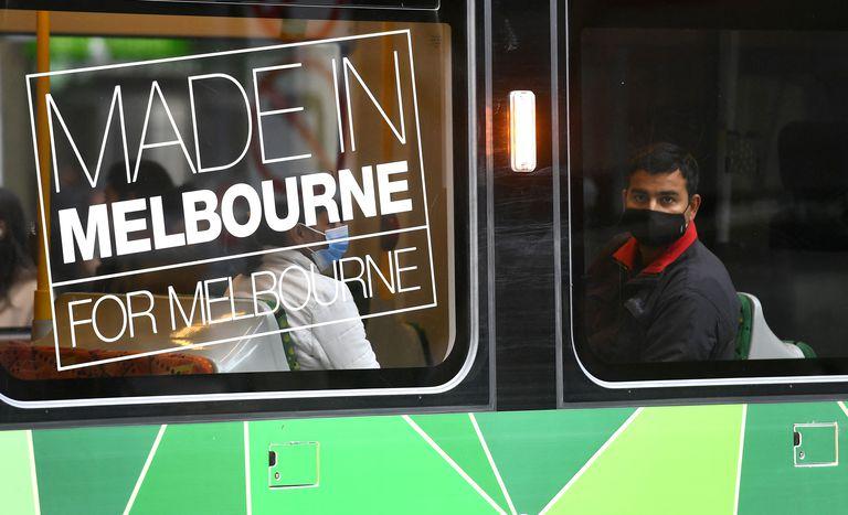 Un hombre con mascarilla en el tranvía en Melbourne