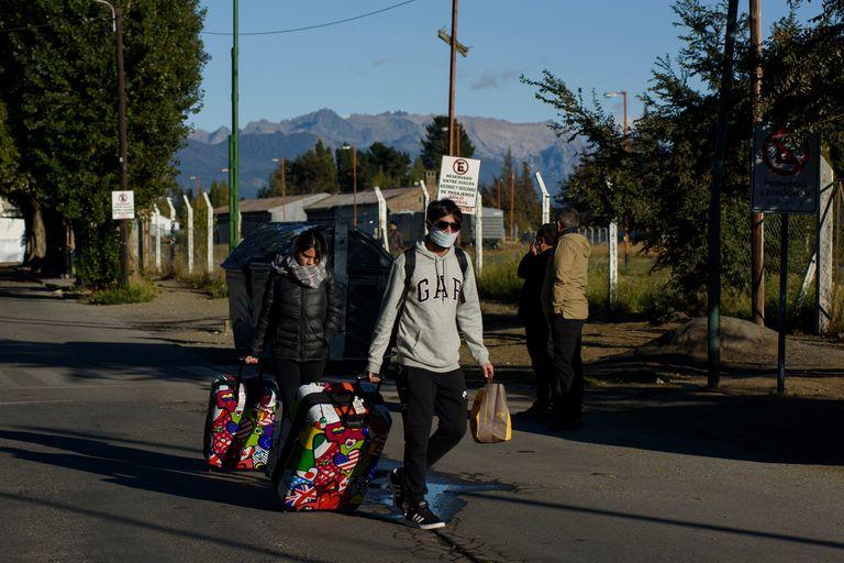Una pareja se dirige a la terminal de ómnibus de Bariloche, para empezar el viaje de regreso
