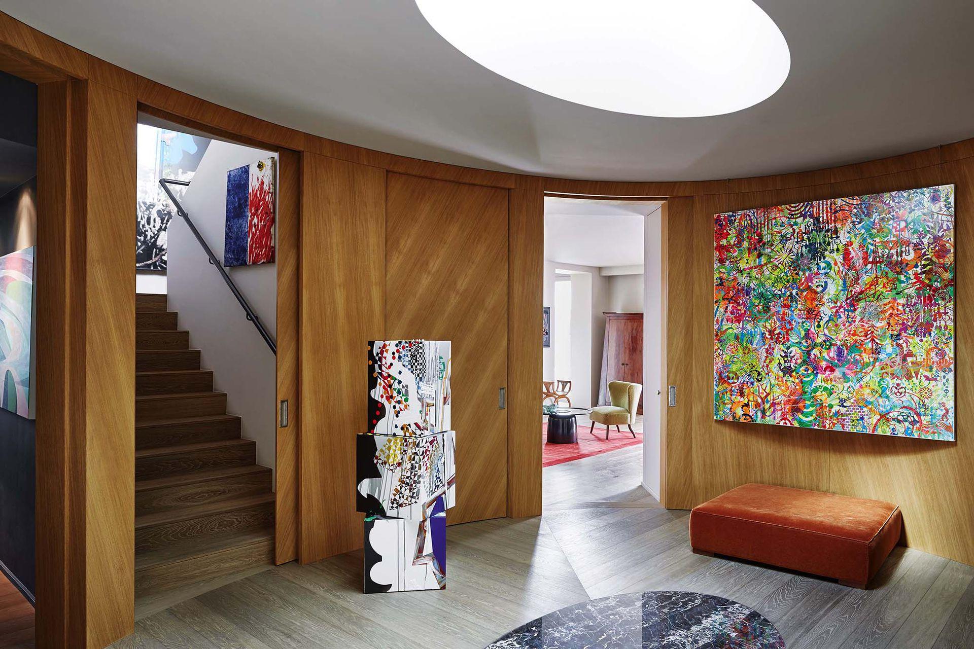 El hall es el centro neurálgico de la casa. En medio del piso de roble ahumado, un óvalo de mármol reitera la forma de la claraboya que ilumina todos los ambientes.