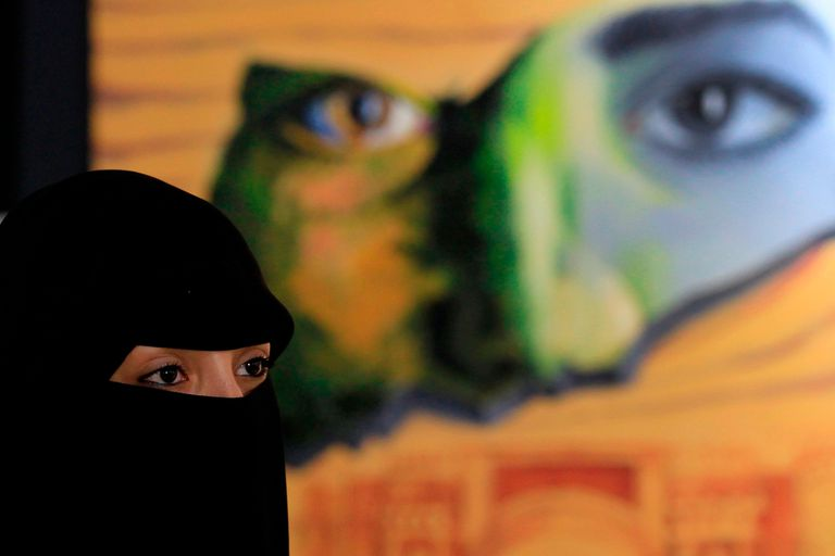 A Yemeni woman visits an art exhibition against war by Yemeni painters at the Peoples Development Foundation in the Yemeni capital of Sanaa on October 1, 2018. - About 24 Yemeni artists participated with more than 100 pieces of art work in an exhibition in Sanaa to attract attention to the ongoing w