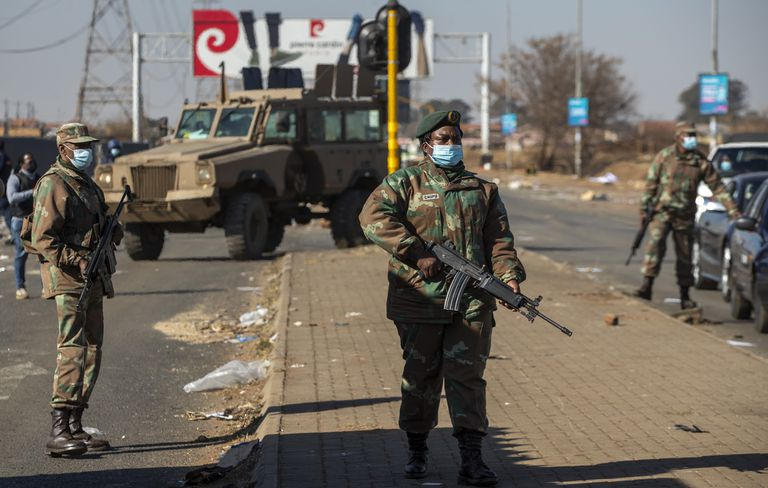 Un soldado observa mientras los líderes comunitarios hablan a un grupo de hombres en un esfuerzo por evitar que entren en un centro comercial en Vosloorus, al este de Johannesburgo, Sudáfrica.