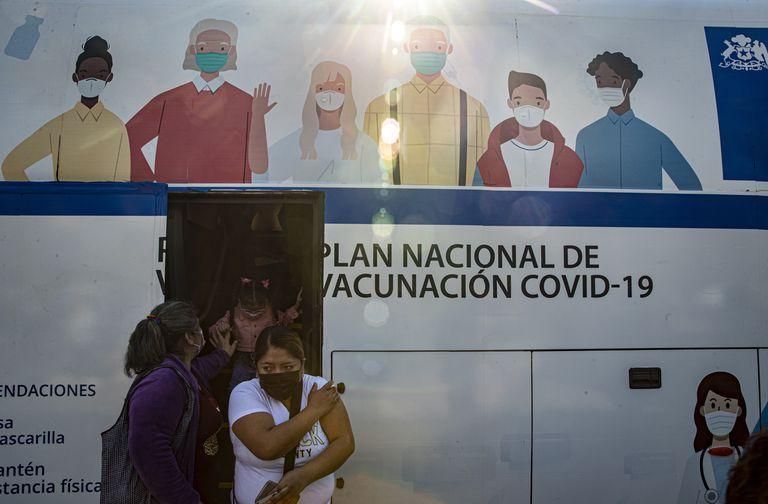 Mujeres salen de un ómnibus que se usa para inyectar la vacuna contra Covid-19 en Santiago, Chile