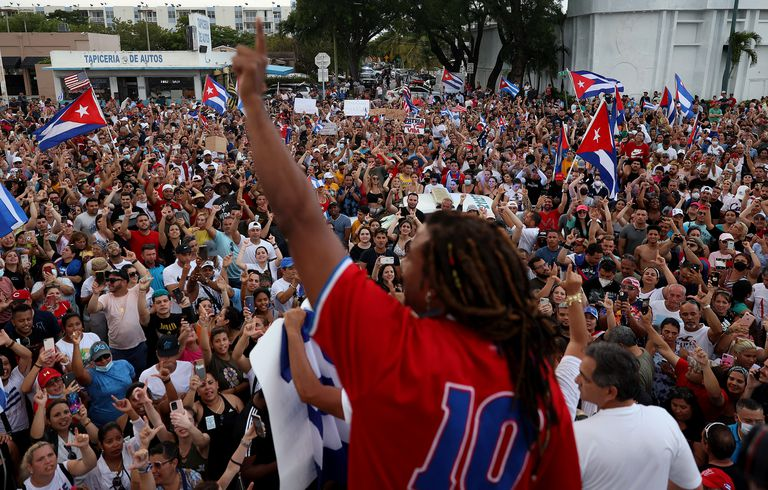 El cantante Yotuel Romero (C) se dirige a los manifestantes reunidos frente al restaurante Versailles mientras muestran su apoyo a la gente en Cuba que ha salido a las calles allí para protestar el 11 de julio de 2021 en Miami, Florida