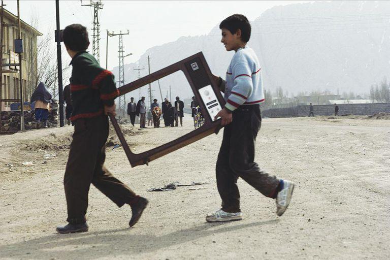 En pantalla. Dos niños kurdos cruzan la calle cargando restos de un televisor (1993)