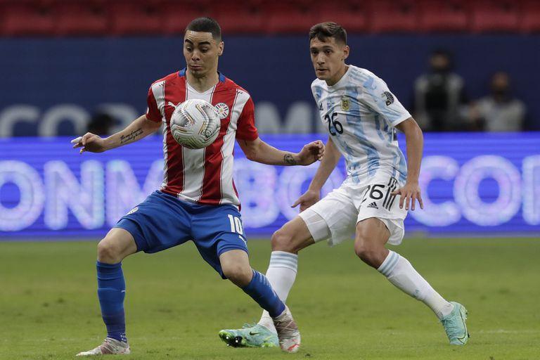 Miguel Almirón de Paraguay, y Nahuel Molina de Argentina luchan por el balón durante un partido de fútbol de la Copa América en el estadio Nacional de Brasilia.