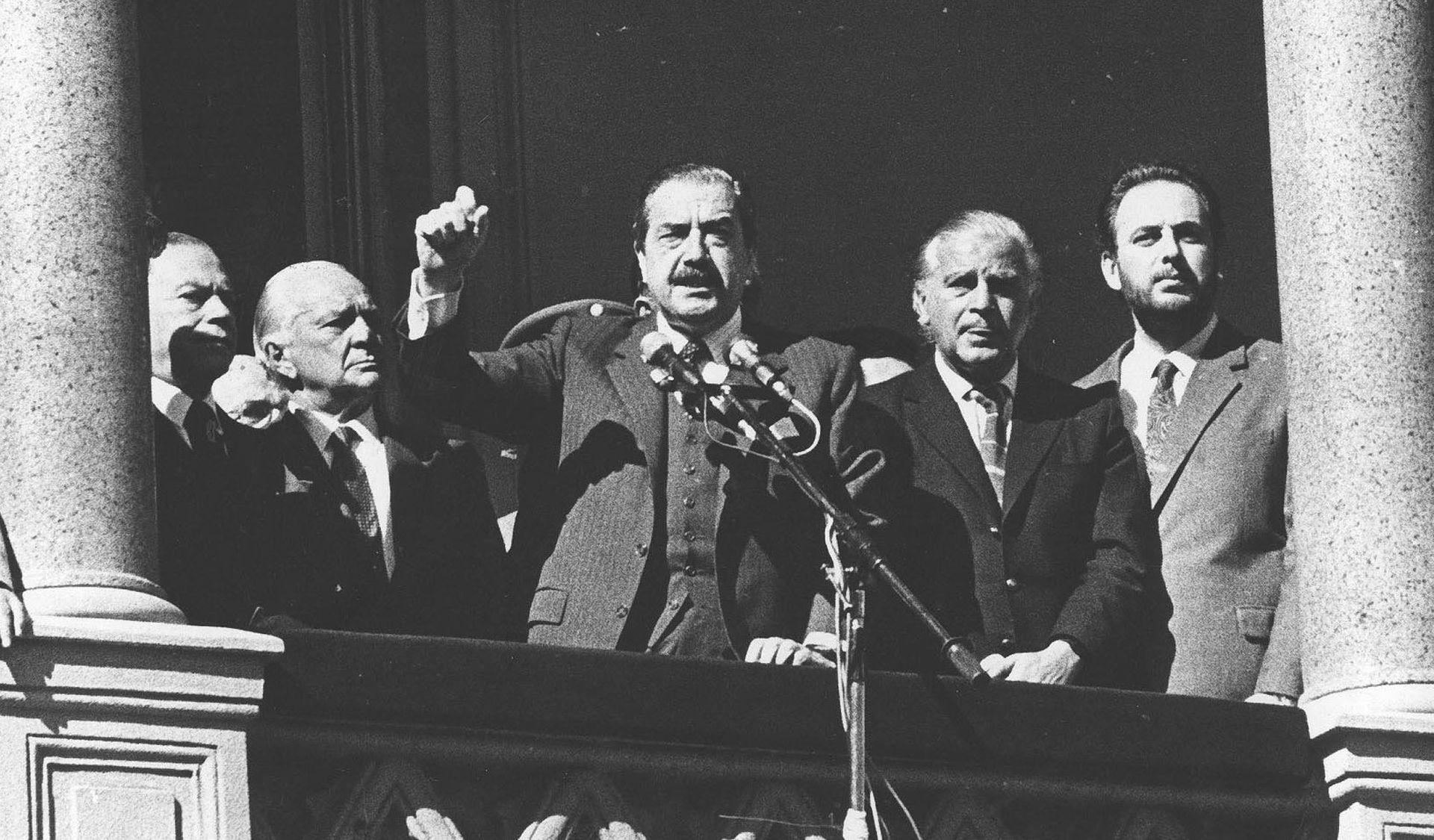 """El 19 de abril de 1987, un hito de la democracia. Desde Casa Rosada, Raúl Alfonsín pone fin a varios días de angustia e incertidumbre por el alzamiento carapintada. """"Felices Pascuas, la casa está en orden"""", dice. Entre los dirigentes políticos que lo acompañaron en el balcón estuvo José Luis Manzano. Una semana después, el dirigente justicialista cambió aplausos por insulto..."""