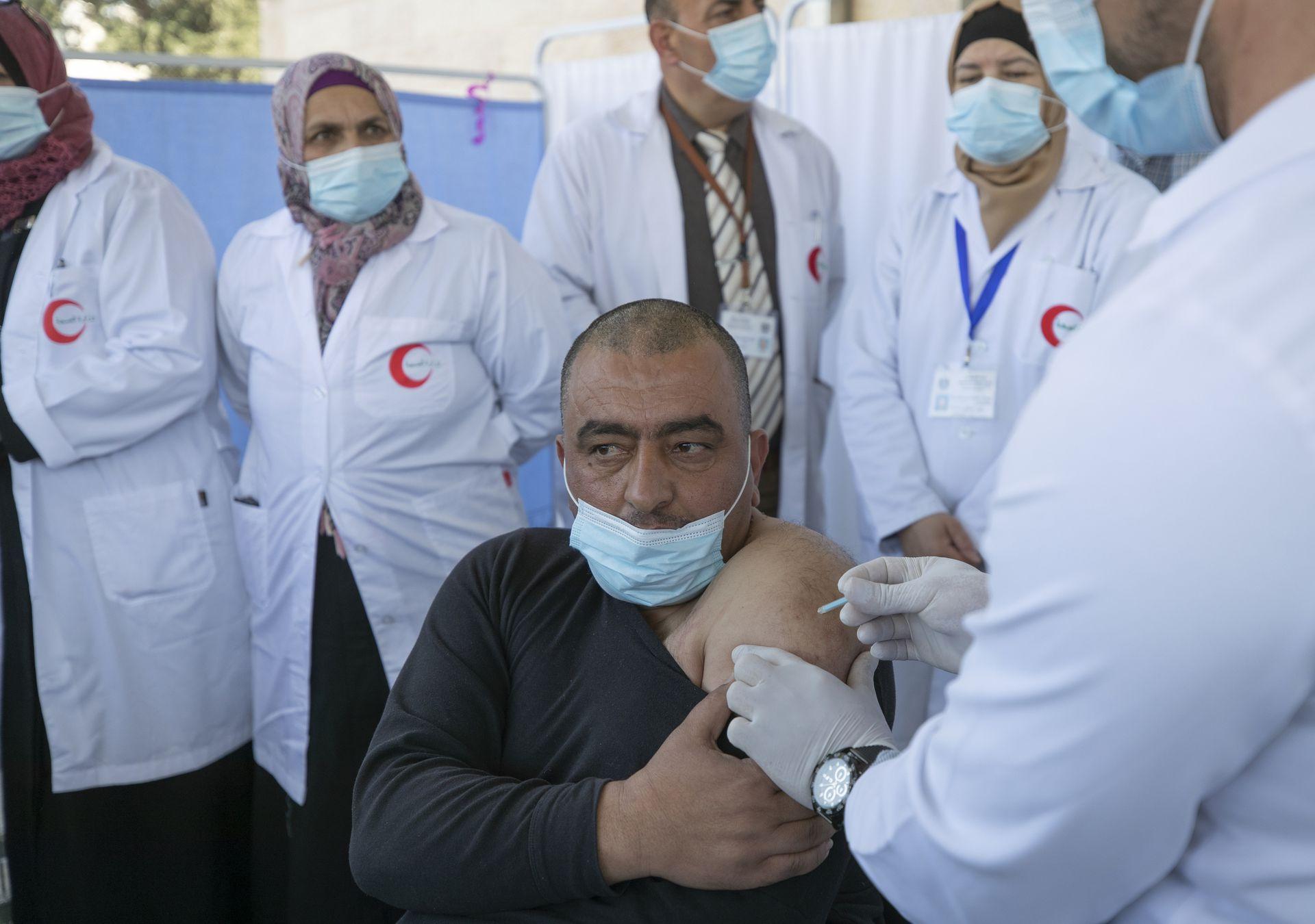 CISJORDANIA: Un médico administra una vacuna Moderna COVID-19 a un compañero médico durante una campaña para vacunar a los trabajadores médicos de primera línea, en el Ministerio de Salud, en la ciudad de Belén en Cisjordania, el 3 de febrero de 2021.