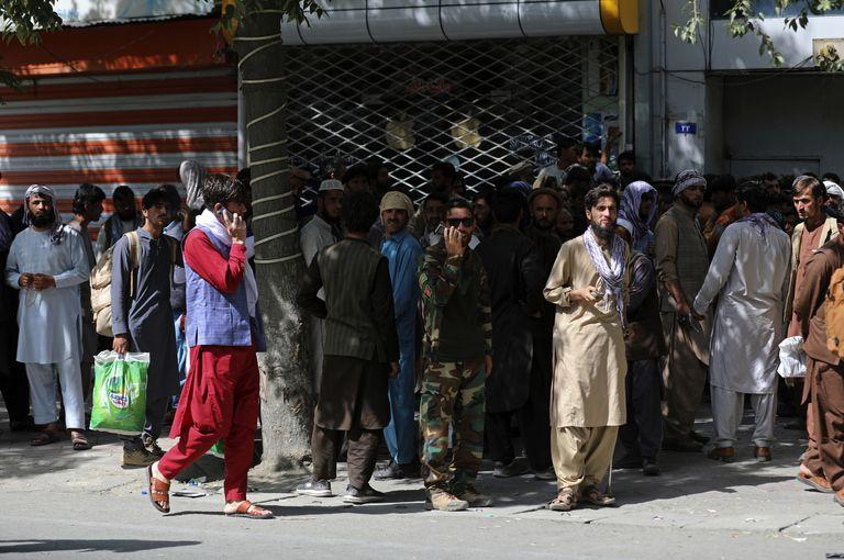 Los afganos esperan en largas filas durante horas para retirar dinero, cerca del Kabul Bank, en Kabul, Afganistán, el domingo 15 de agosto de 2021. Los combatientes talibanes ingresaron a Kabul y buscan la rendición incondicional del gobierno central