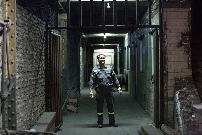 Diego Jezierski, trabajador de mantenimiento, en la estación Pasco Sur; a su derecha, la pared que oculta la estación a los pasajeros