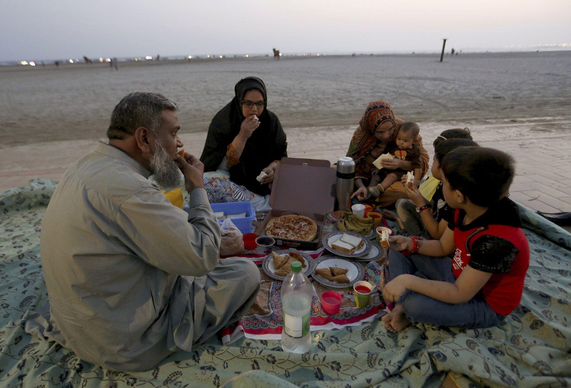 Una familia acaba su ayuno en la playa de Clifton en Karachi, Paquistán