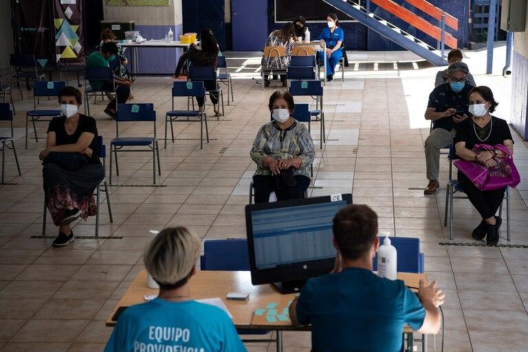 Las personas esperan su turno para ser inoculadas contra la Covid-19 en un centro de vacunación en Santiago de Chile, el 01 de marzo de 2021