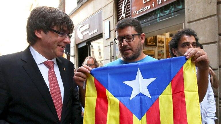 El presidente de Cataluña, Carles Puigdemont, en Barcelona, con un simpatizante de la independencia