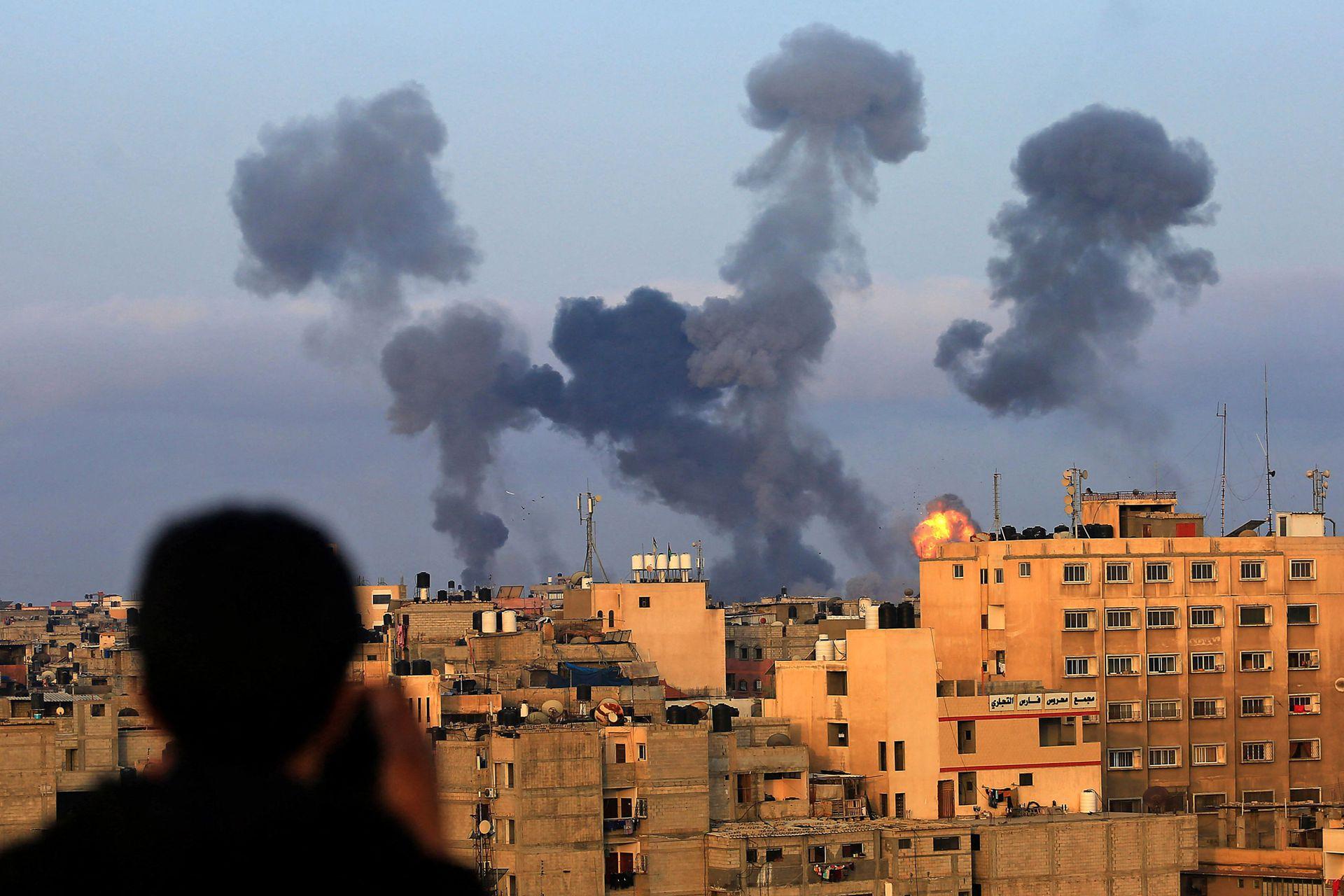 Un niño palestino observa humo saliendo de edificios durante los ataques aéreos israelíes en la región de Khan Yunis, en el sur de Gaza