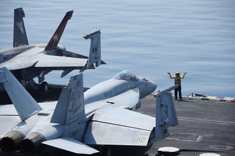 Cazas F/A-18C a punto de despegar del portaaviones George H.W. Bush, en el Golfo