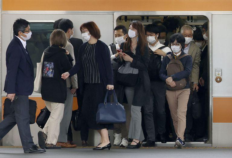 Pasajeros con mascarillas para protegerse del coronavirus salen de un tren en Tokio. Los casos en Japón siguen en aumento