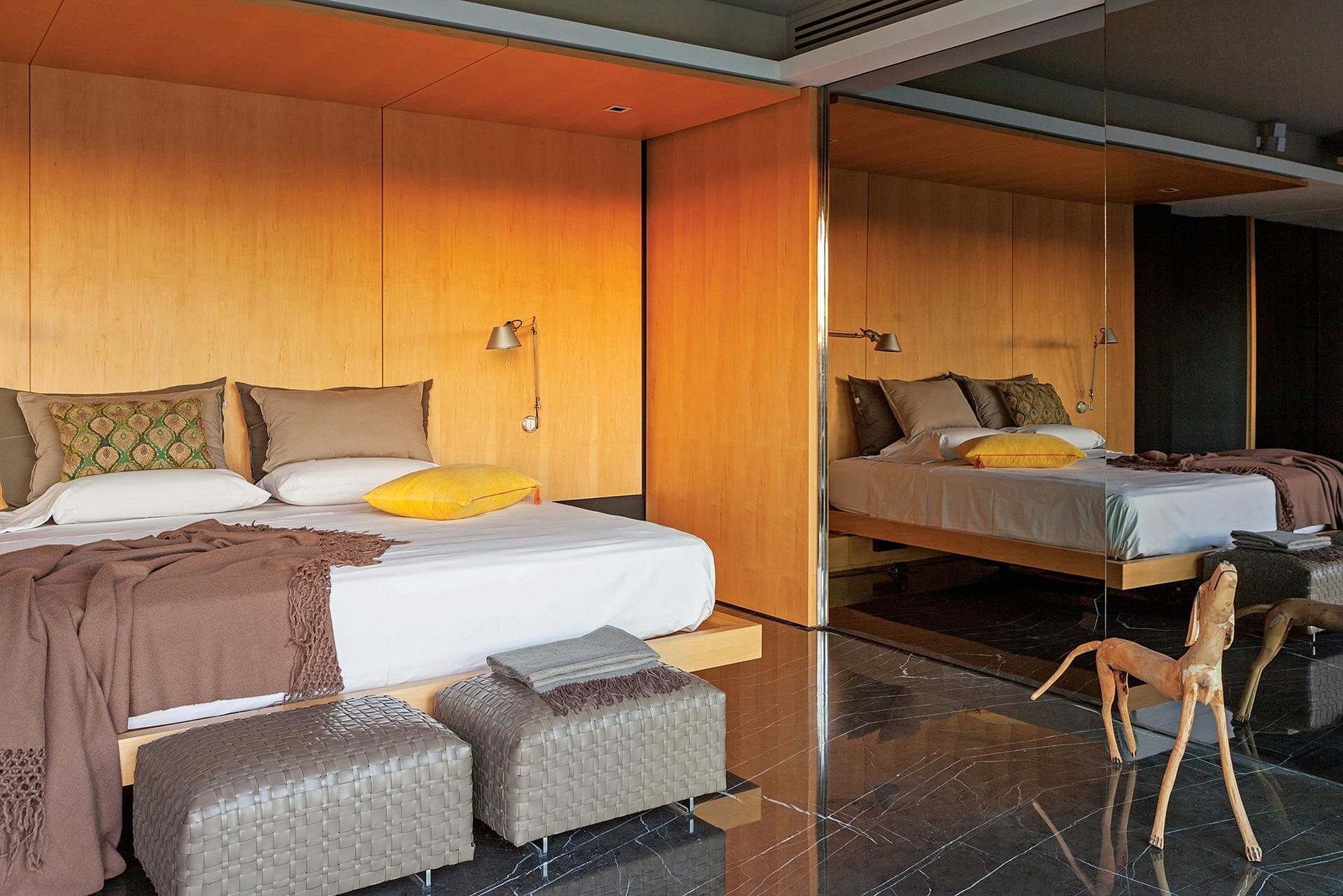 Al costado de la cama se encuentra el vestidor con puertas de vidrio fumé. Lámparas de brazo flexible (Griscan). Butacas (Flexform).