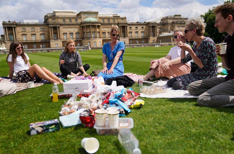 Visitantes disfrutan de un picnic en el césped durante una visita previa por el Jardín del Palacio de Buckingham, la residencia oficial de la reina Isabel II en Londres, que se abre al público el viernes