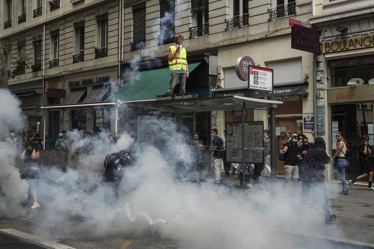 Manifestantes están parados en medio de bengalas de humo delante de policías en una protesta en Lyon el sábado, 31 de julio del 2021. Manifestantes salieron a las calles en  varias ciudades francesas para protestar contra el pase del COVID-19, que les da a los individuos vacunados mayor acceso a instalaciones. (AP Foto/Laurent Cipriani)