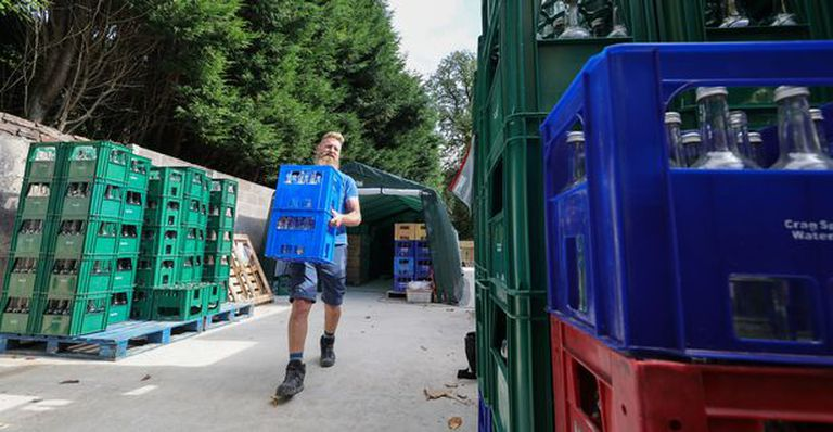 Binder tranasportando los cajones de botellas de agua