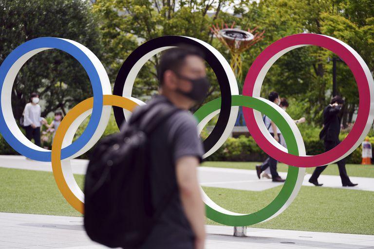 En foto del miércoles 2 de jjnio del 2021, la gente camina junto a los aros olímpicos en tokio. El martes 8 de junio del 2021, el COI da conocer la lista de 29 atletas que formarán parte del equipo de refugiados en los Juegos Olímpicos. (AP Photo/Eugene Hoshiko)